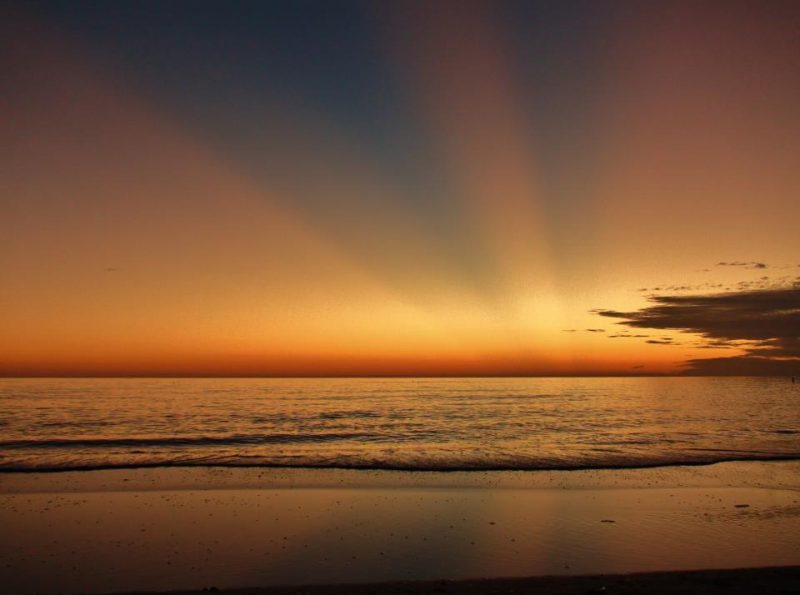 Orange rays projecting over an ocean.