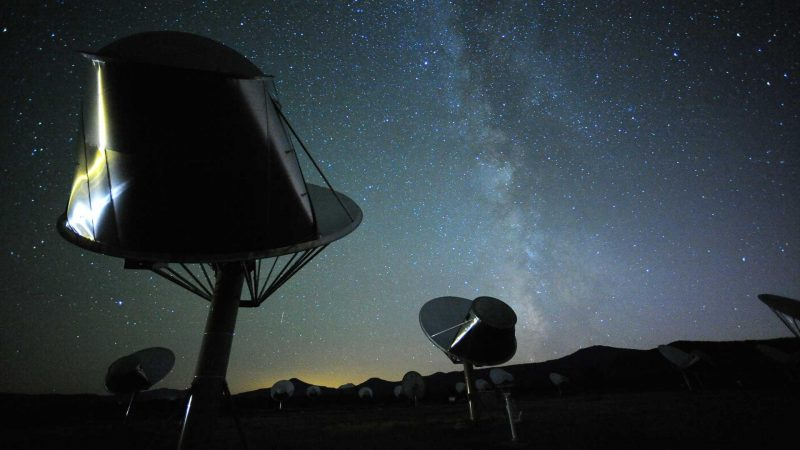 Two dish-type radio antennas with the Milky Way in the background.
