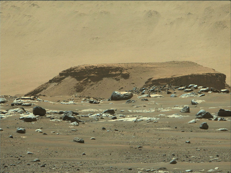 Rocky outcrop with larger hill behind it and boulders at its base.