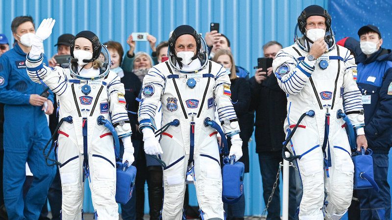 1st movie in space; One woman and two men dressed in white suits, with masks covering their noses and mouths, walk and wave to a crowd around them.