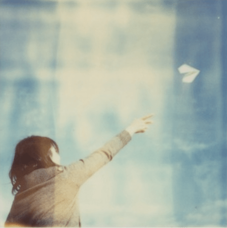 filtered photograph of young girl throwing paper airplane into sky