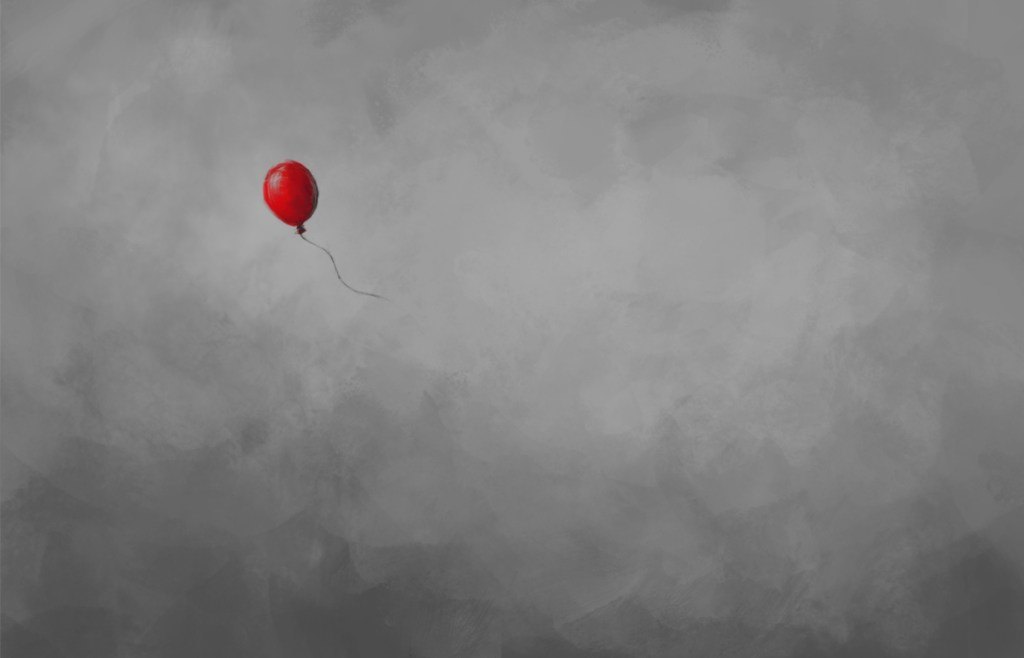 single red balloon floating through a gray sky