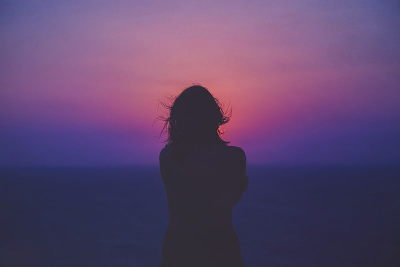 Silhouette of a woman hugging herself against a pink and purple sunset