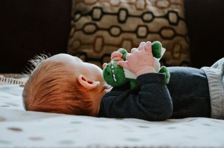 baby lying on his back holding a stuffed dinosaur