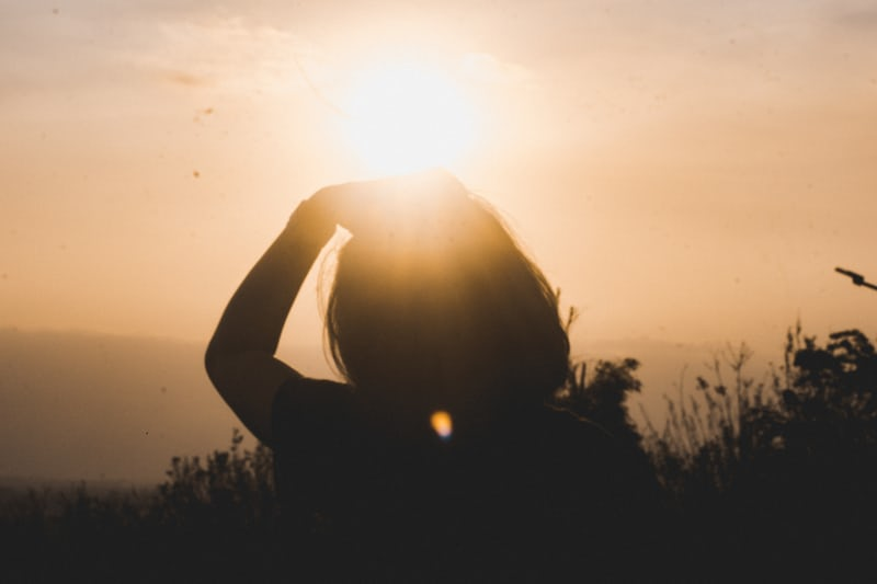 silhouette of woman from the back with hand on head in the sunset