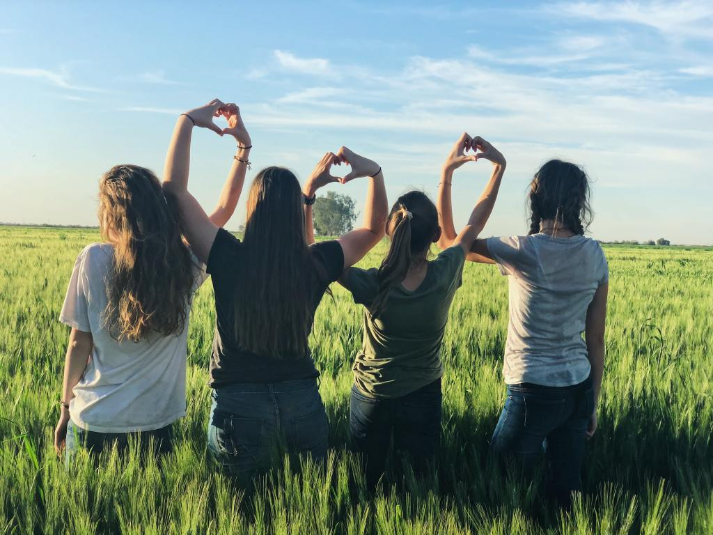 girls in a field making heart gestures with their arms