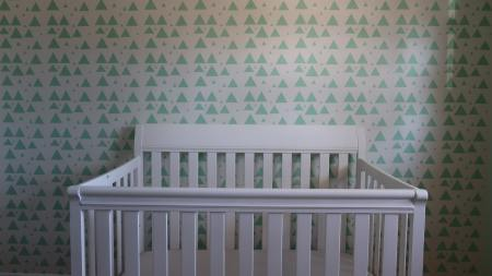 empty crib against green triangle wallpaper