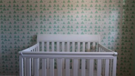 empty crib against green triangle wallpaper