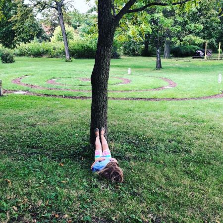 little girl lying on her back with feet up against a tree