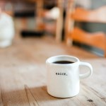 white mug of coffee with word begin on it