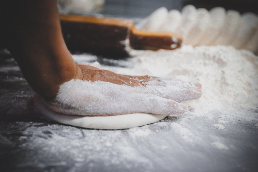 hand kneading dough in flour