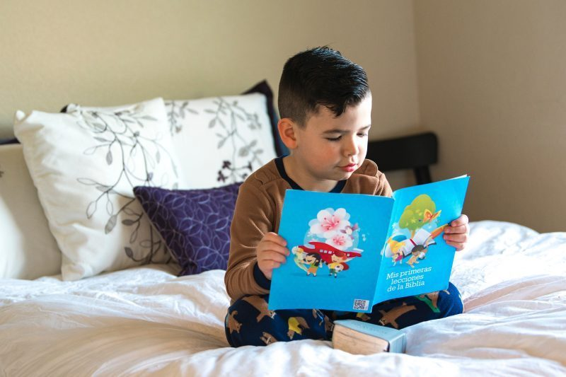 boy sitting on bed reading