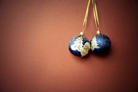 two christmas baubles against brown background