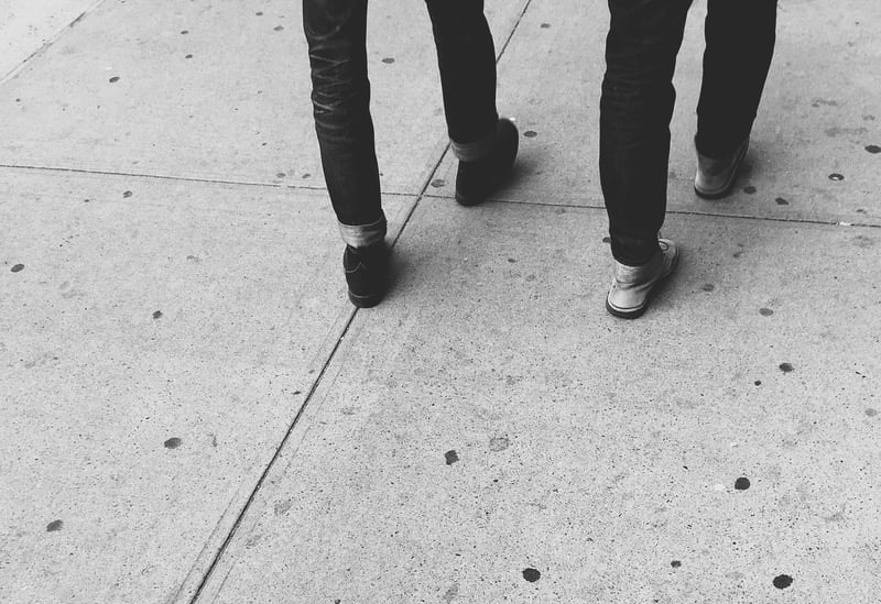 black and white two people's leg walking on pavement