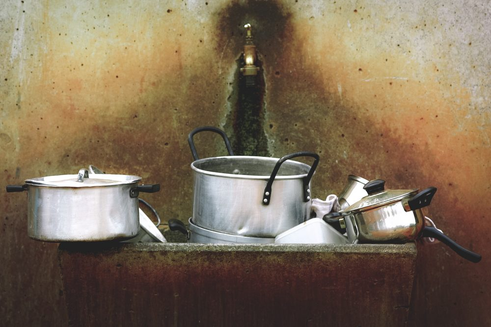 silver pots unwashed in a sink