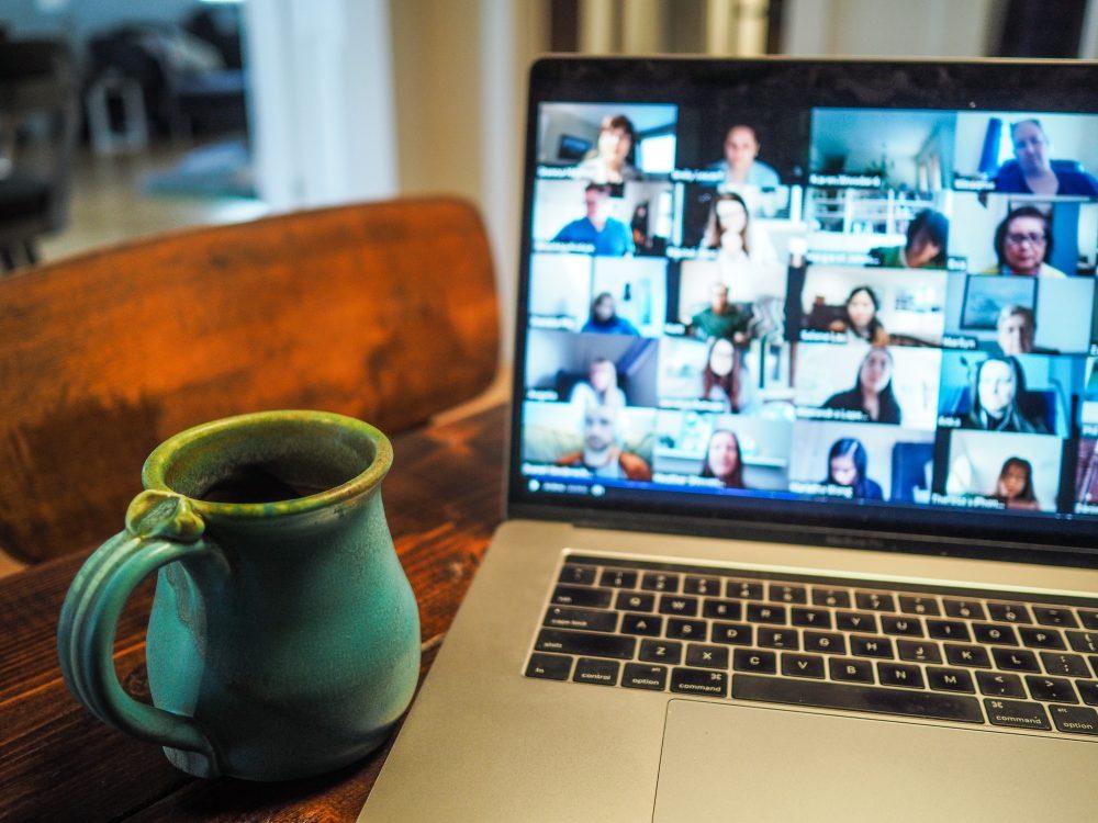 Zoom call with coffee mug next to laptop