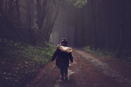 little girl walking by herself in the woods