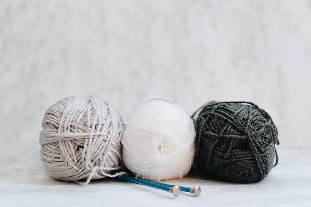three balls of wool and knitting needles