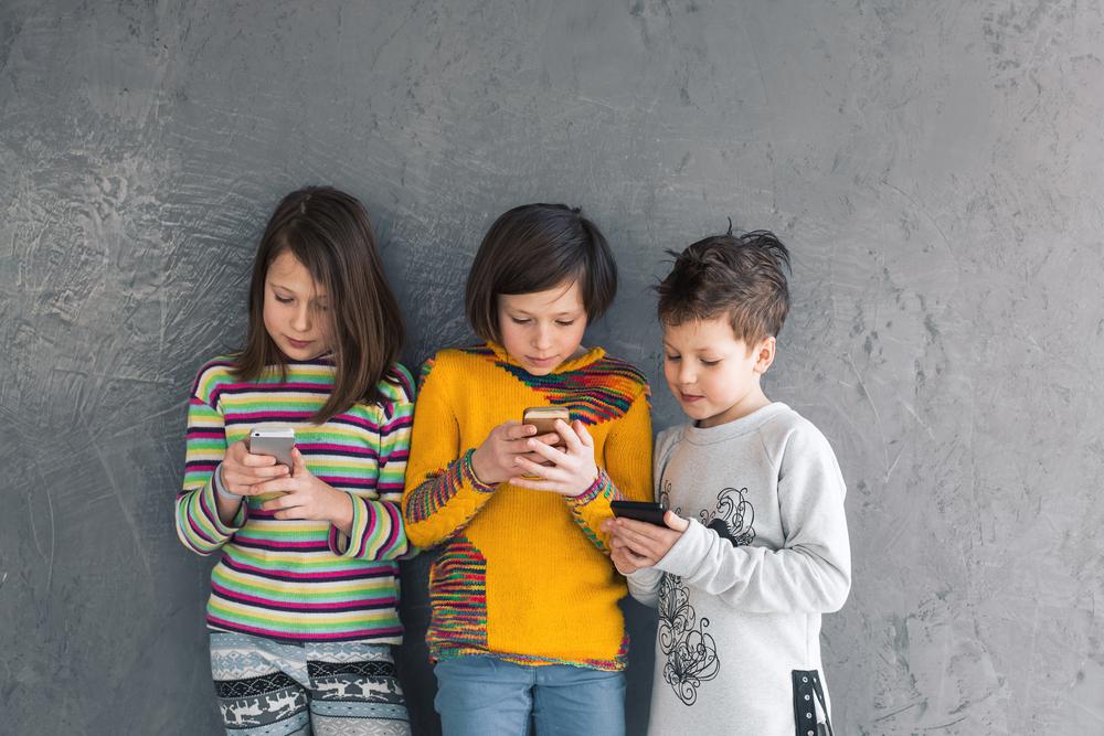 Three kids looking at phones
