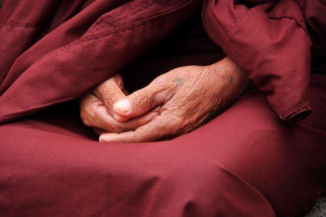 Weiterentwicklung - Gefaltene Hände eines Mönchs