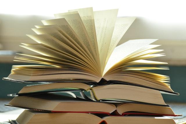 Bachelorarbeit schreiben - Ein aufgeklapptes Buch auf einem Buchstapel