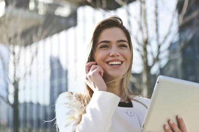 Persönliche Weiterentwicklung - Lachende Frau mit Ipad