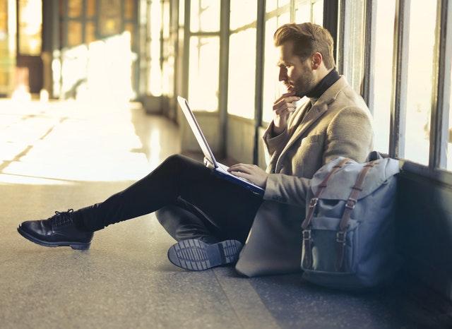 Persönliche Weiterentwicklung - Mann mit brauner Jacke sitzt am Flughafen mit Laptop