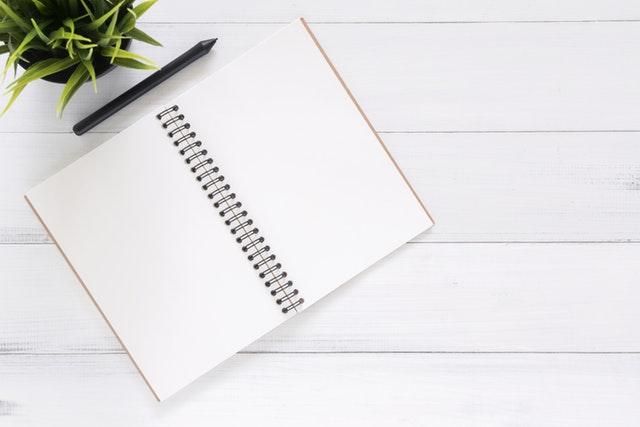 Positives Denken lernen - Tagebuch neben einer Pflanze