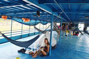 Девушка у гамака и палатки на палубе корабля в Амазонке