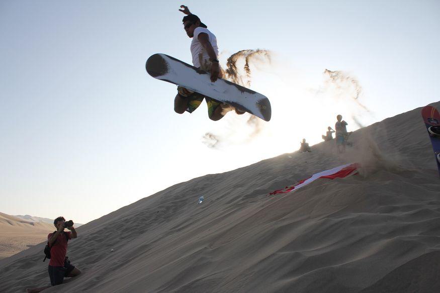 Парень прыгает на сэндборде для фото в Уакачине в Перу