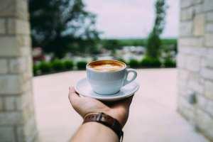 чашка кофе на вытянутой руке