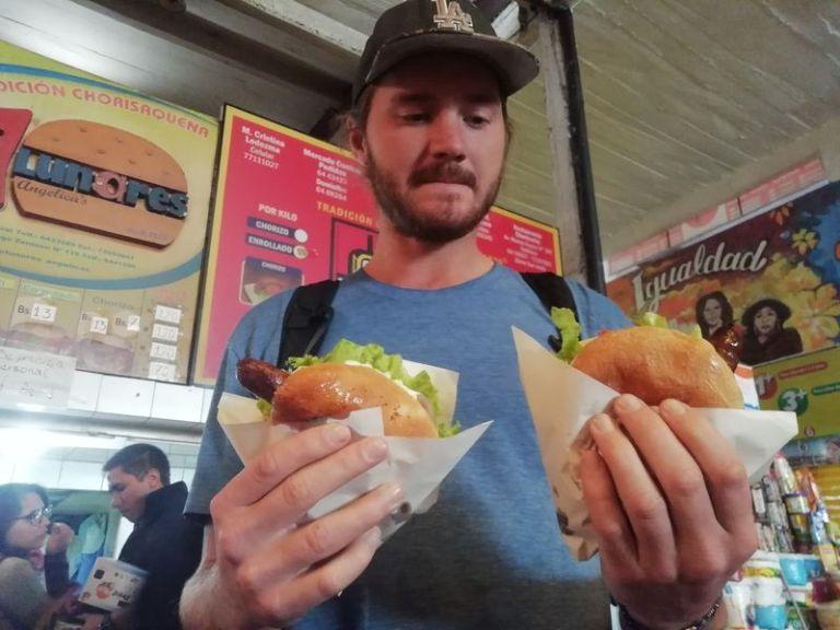 Мужчина держит в руках сендвич