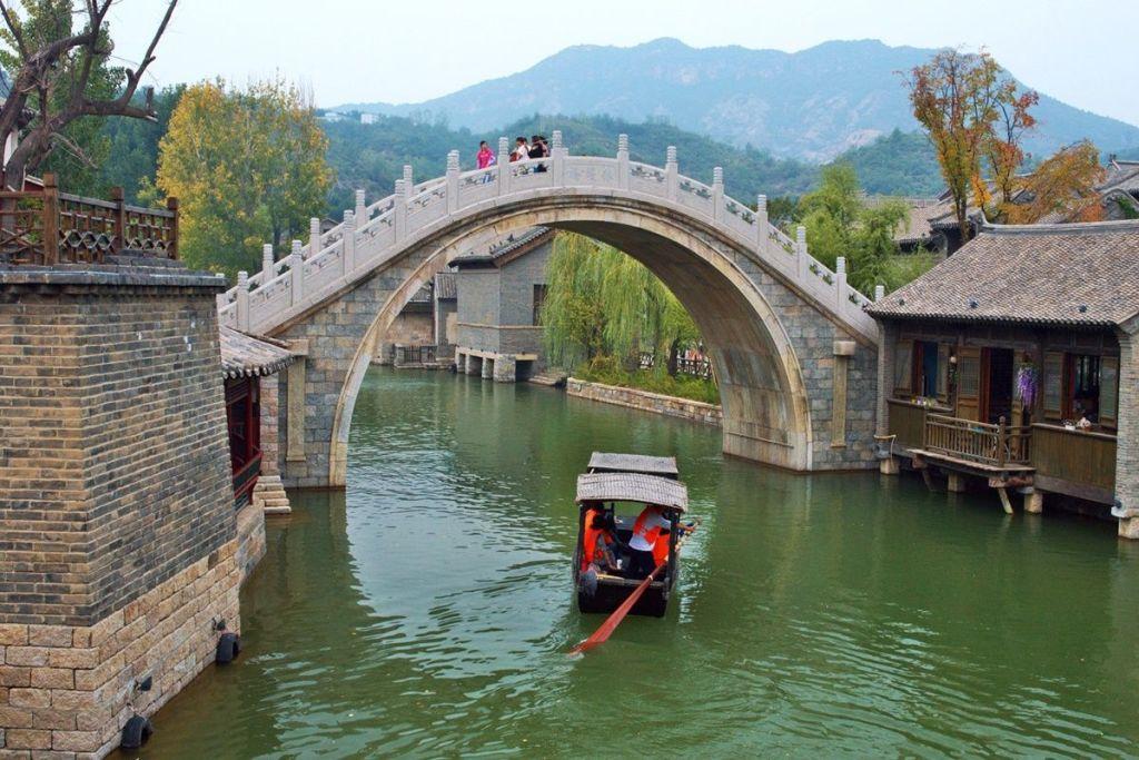 Прогулка на лодке под арочным мостов