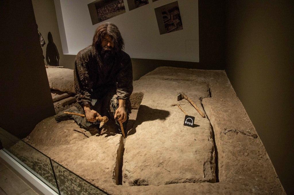 Инсталляция в музее - человек обрабатывает камень