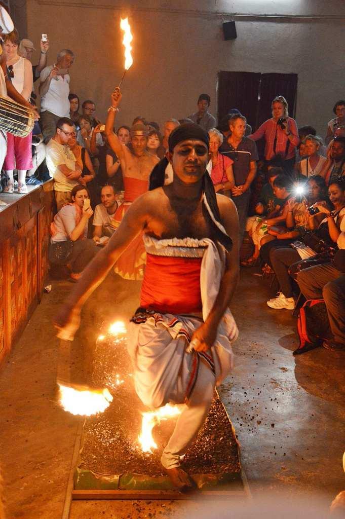 Мужчина наступает босой ногой на огонь