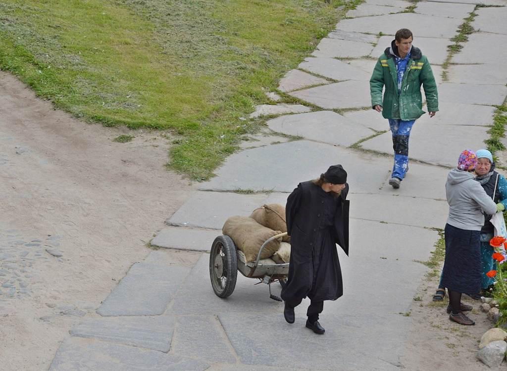 Монах везет мешки на тележке