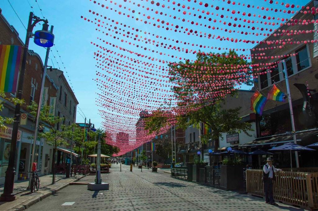 Улица с розовыми фонариками и радужными флагами
