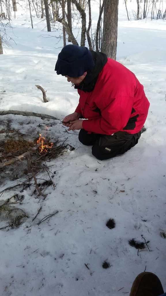 Мужчина разводит огонь на снегу
