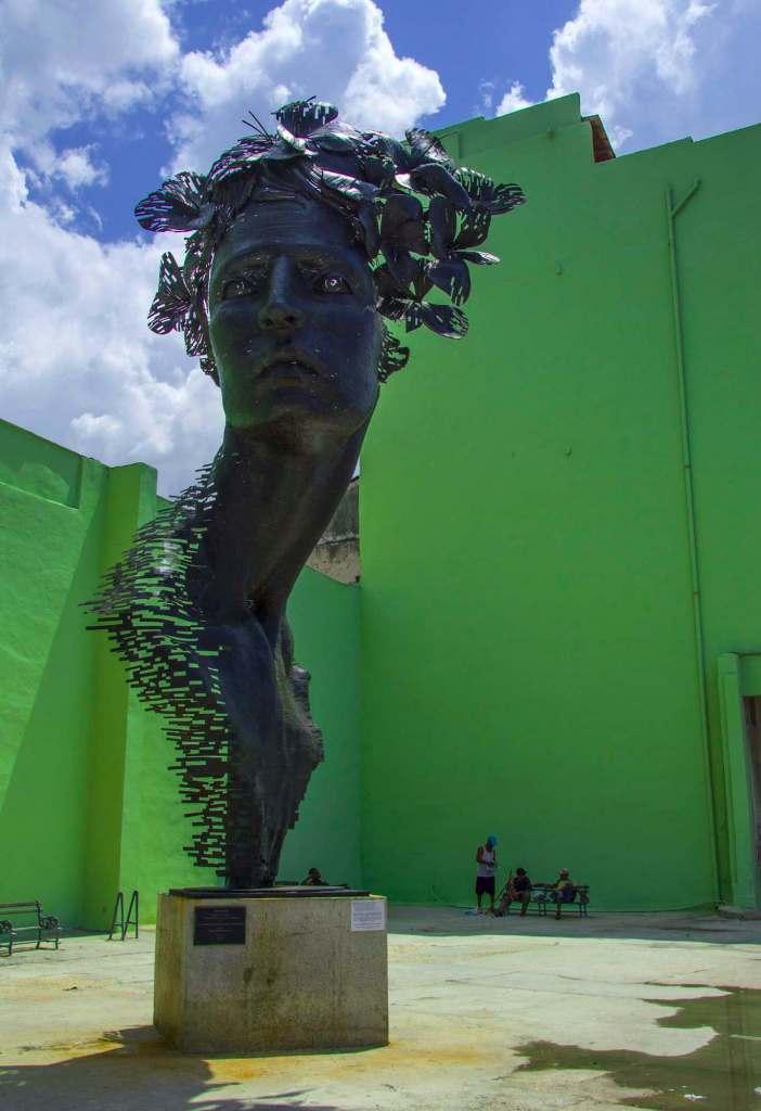 Памятник на фоне зеленой стены