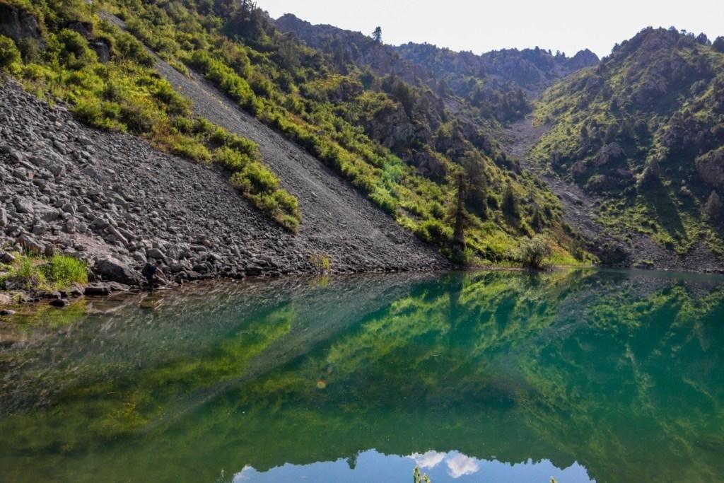Горное озеро — отражение скалы в воде