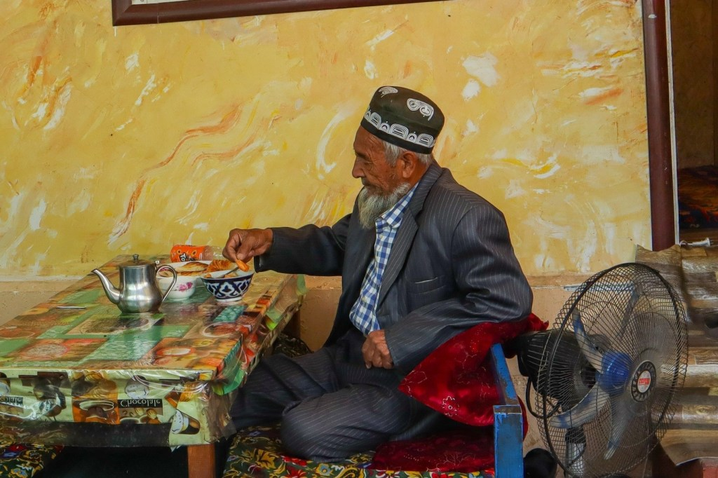 Киргиз в традиционной шапке ест в ашкане