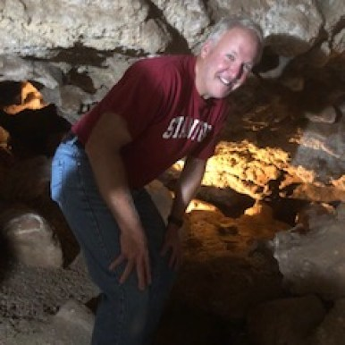 Mike is so tall, he has to crouch down inside a cave in Sturgis