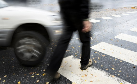 pedestrian crossing in autumn, in danger of being hit by car