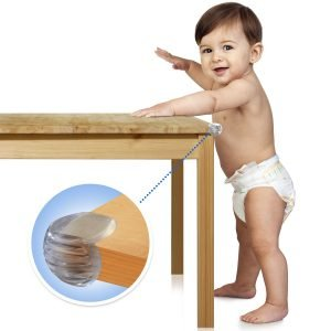 A baby leaning on a table fitted with furniture babyproof corner safety protector
