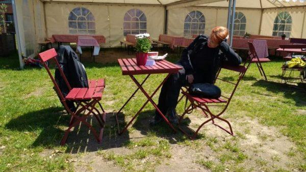 Rothaarige Motorradfahrerin in einem Gartenlokal beim langen Warten auf das Essen