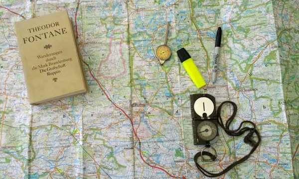 Motorradreisen erleben schon vei der Vorbereitung: Landkarte mit Kompass, Stifzen und einem Band von Theodor Fontanes Wanderungen durch die Mark Brandenburg