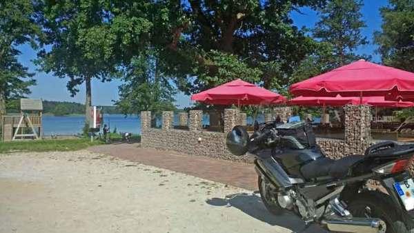 Yamaha FJR 1300 neben einer Caféterrasse mit roten Sonnenschirmen am See bei einer Motorradtour zur Havelquelle