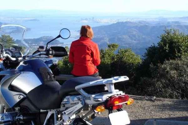 Rothaarige Motorradfahrerin in roter Kombi vor einer BMW R 1200 GS mit Blick vom Mt. Tamalpais auf die San Francisco Bay in Kalifornien - eine Szene der Harmonie mit der Sozia im Sattel