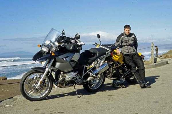 Junger Mann mit seinem gelben Motorrad Ducati Monster 750 bei einem Technischer Halt auf der CA 1 bei der Skyline Boulevard Motorradtour in Kalifornien