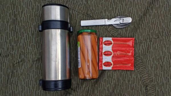 Thermosflasche, eines Glases Wiener Würstchen, einer Dreierpackung Senf und eines Feldessbestecks als deftige Methode fuer Essen auf Rädern im Winter